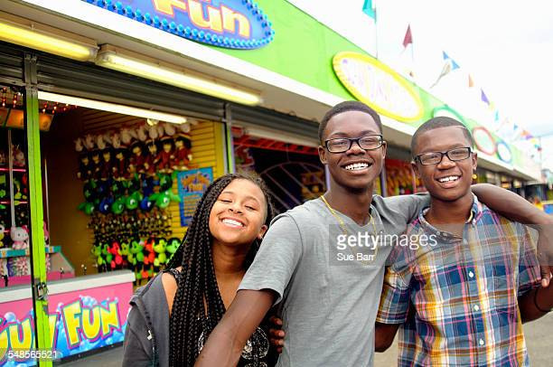 Portrait of teenage boys and sister at amusement park