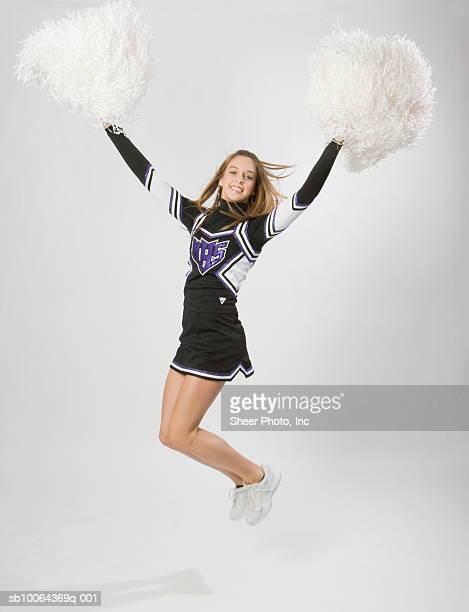 portrait of teenage (14-15) cheerleader jumping, mid air - cheerleader up skirt stock photos and pictures