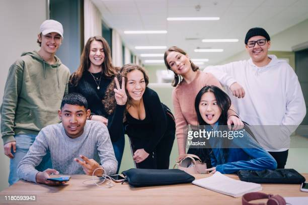 portrait of teenage classmates making faces at desk in classroom - hoofd schuin stockfoto's en -beelden
