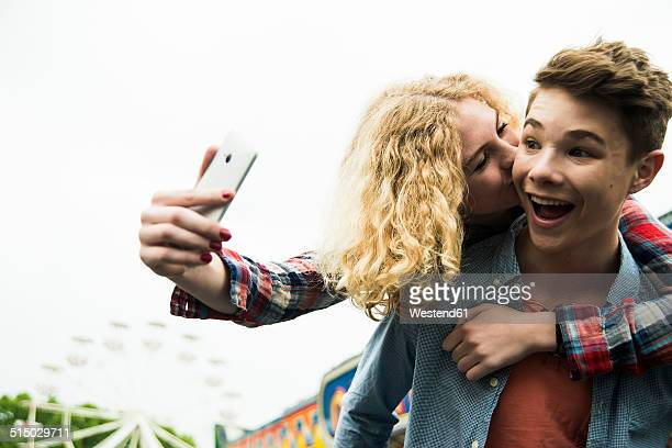 Portrait of teenage couple photographing themself at fun fair