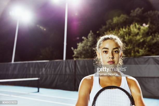 Portrait of teenage female tennis player after practice on outdoor court at night