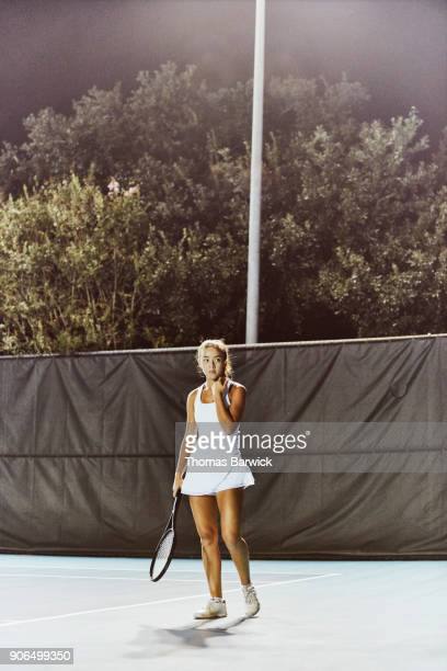 Portrait of teenage female tennis player on outdoor court at night