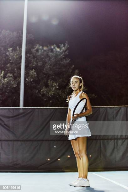 Portrait of teenage female tennis player practicing on outdoor court at night