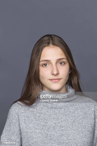 Portrait of teenage girl against gray background