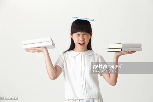 Portrait Of Teenage Girl Balancing Books On Head And Hand While Standing Against White Background