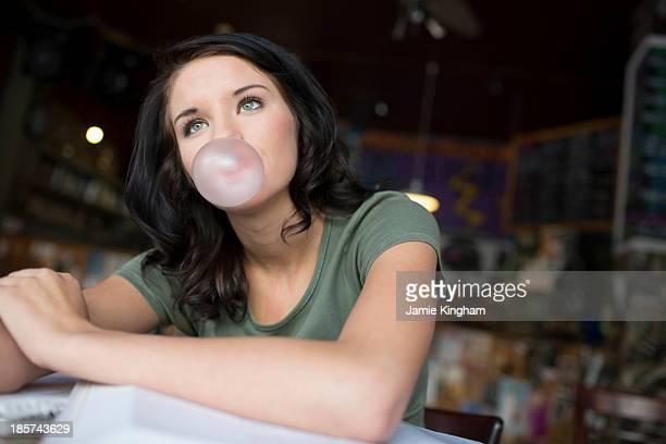 Portrait of teenage girl blowing bubblegum in coffee house