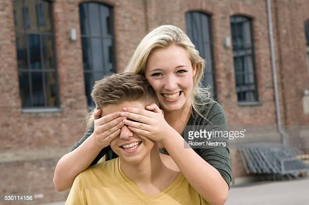 portrait of teenage girl covering eyes of teenage boy, smiling - augen zuhalten stock-fotos und bilder