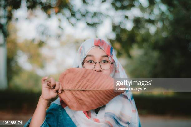 portrait of teenage girl covering mouth with dry leaf - dry mouth stock photos and pictures