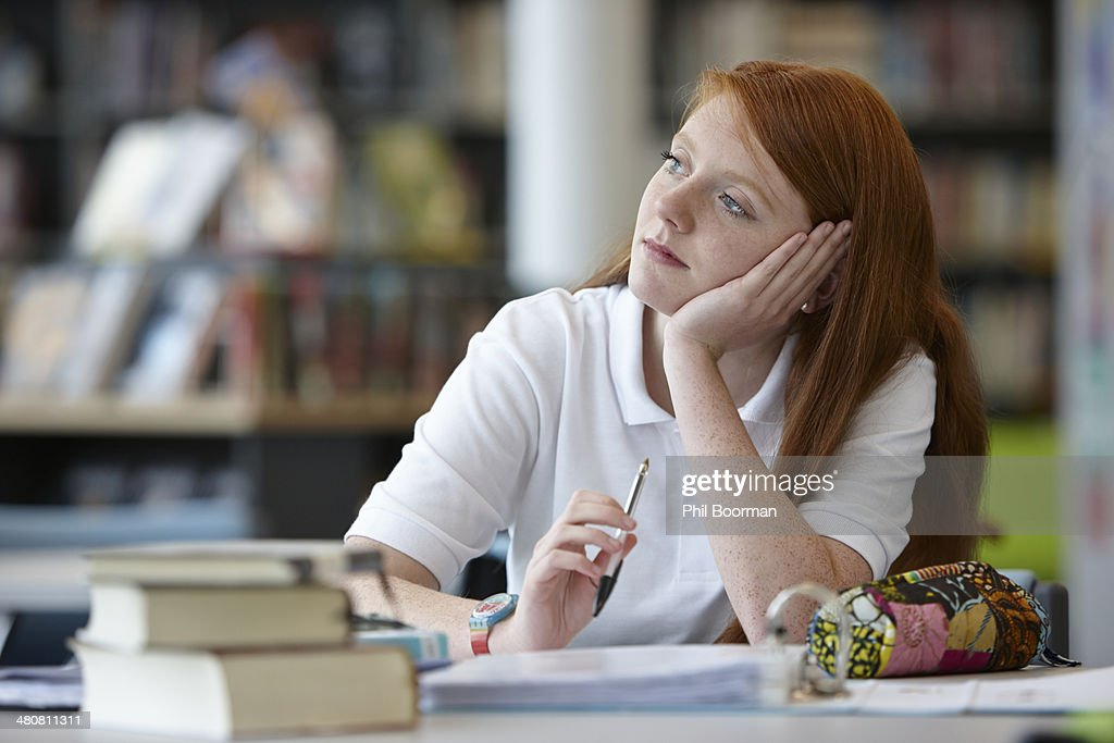 Portrait of teenage girl daydreaming in library : Stock Photo