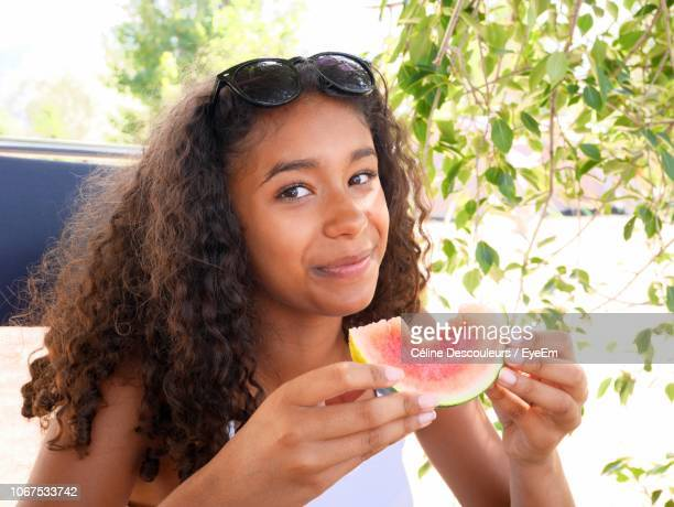 Portrait Of Teenage Girl Eating Watermelon While Sitting Outdoors