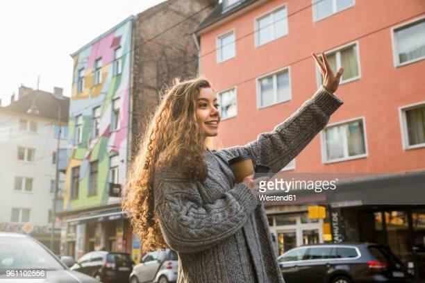 Portrait of teenage girl hailing taxi