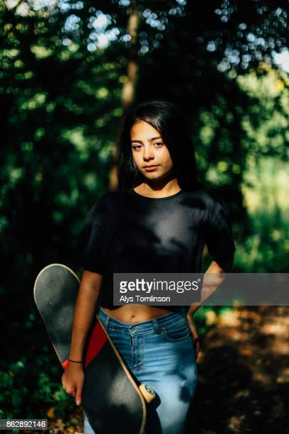 portrait of teenage girl holding skateboard - tee sports equipment stock photos and pictures