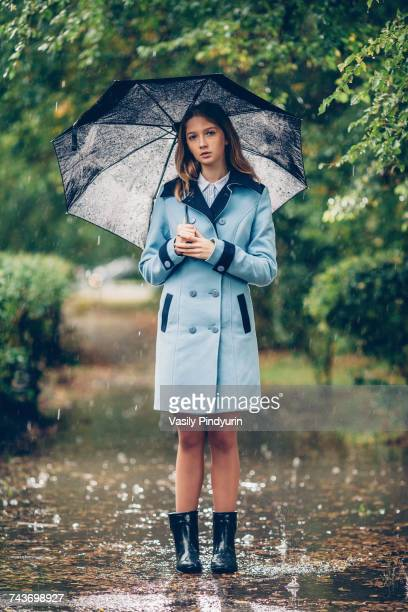 Portrait of teenage girl holding umbrella while standing on pathway amidst trees in rain