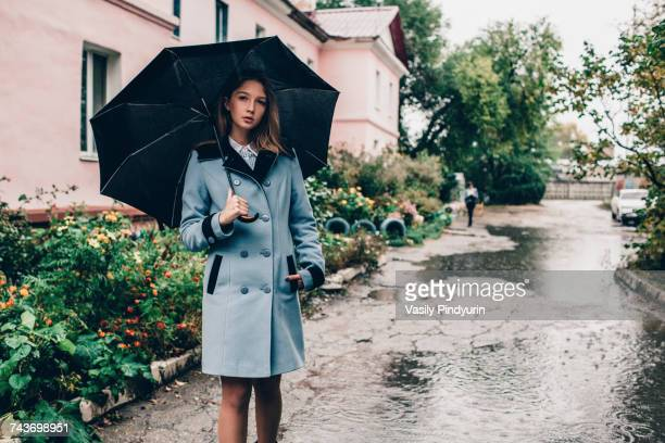 Portrait of teenage girl holding umbrella while standing on wet footpath by buildings in rain