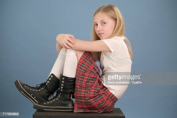 portrait of teenage girl hugging knees while sitting on stool against blue background - little girls up skirt fotografías e imágenes de stock