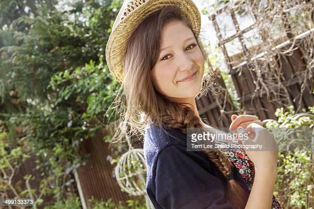 portrait of teenage girl in straw hat in garden - alleen tienermeisjes stockfoto's en -beelden