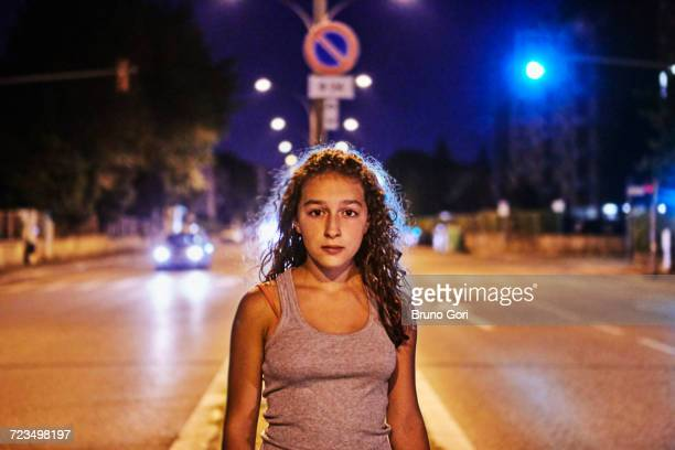 portrait of teenage girl in the middle of the road looking at camera - runaway stock pictures, royalty-free photos & images