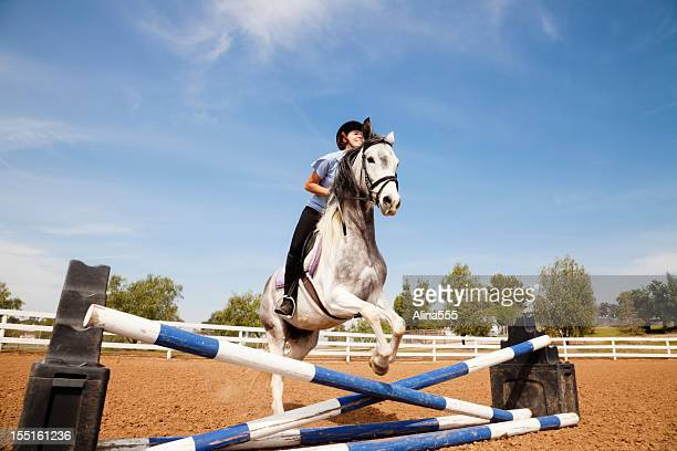 Portrait of teenage girl jumping on a horse