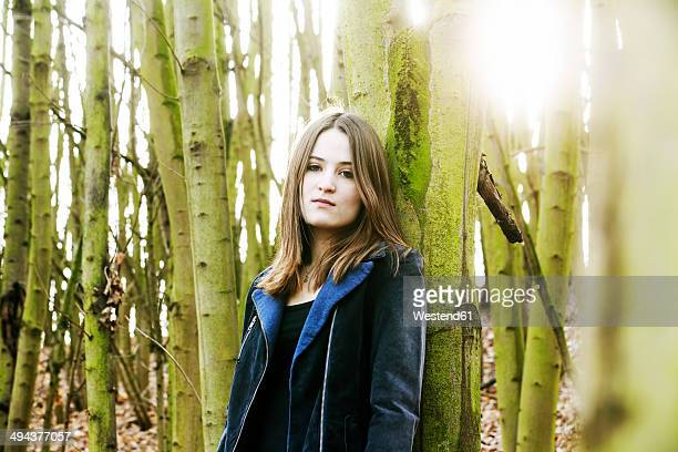 Portrait of teenage girl leaning against tree trunk