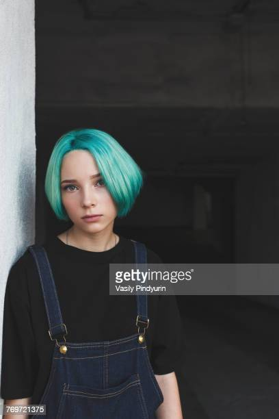 portrait of teenage girl leaning on wall at basement - green hair stock pictures, royalty-free photos & images