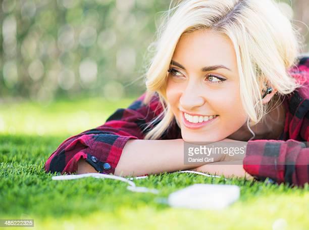 Portrait of teenage girl (16-17) lying on grass