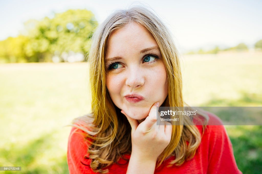 Portrait of teenage girl outdoors doubting : Stock Photo
