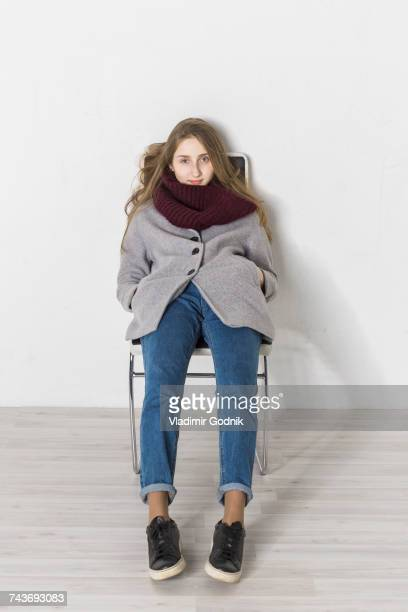 Portrait of teenage girl reclining on chair against white wall