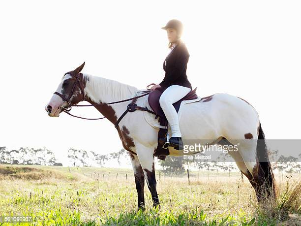 Portrait of teenage girl riding horse in field