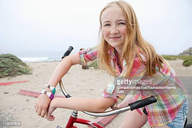 Portrait of teenage girl sitting on bicycle