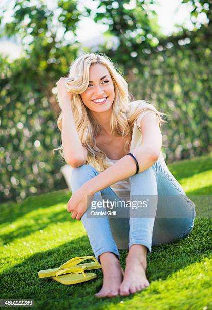 portrait of teenage girl (16-17) sitting on grass - girl wear jeans and flip flops stock photos and pictures