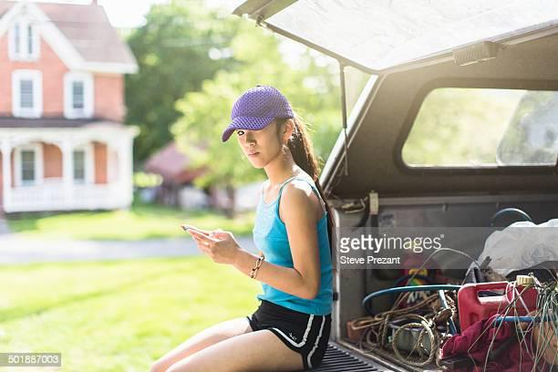 Portrait of teenage girl, sitting on open car boot