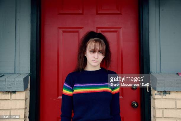 portrait of teenage girl standing by red door - bangs stock photos and pictures