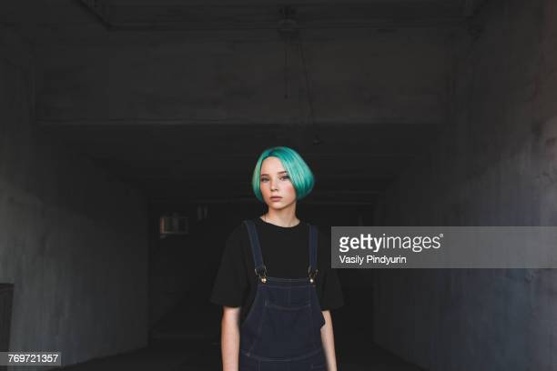 portrait of teenage girl standing in basement - attitude stock pictures, royalty-free photos & images