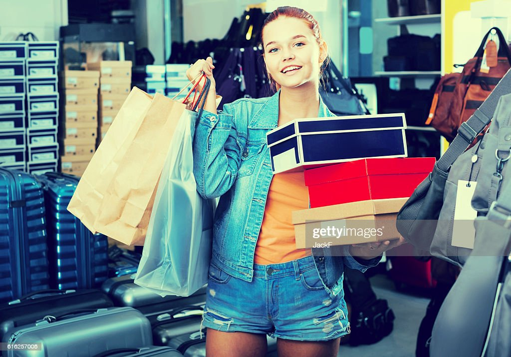 portrait of teenage girl standing with bags in store : Foto de stock