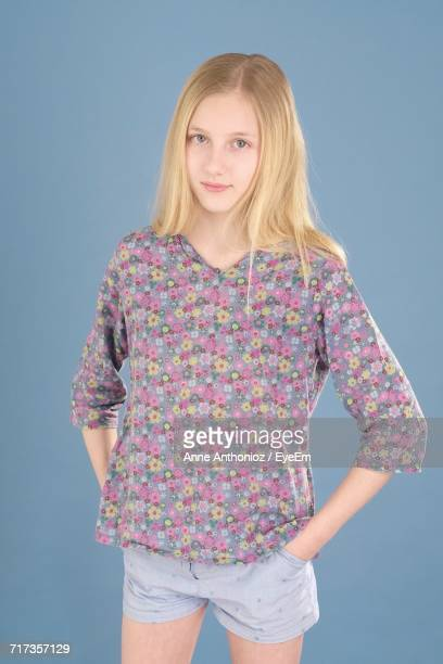 Portrait Of Teenage Girl Standing With Hands In Pockets Against Blue Background