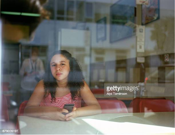 Portrait of teenage girl through window of a cafe