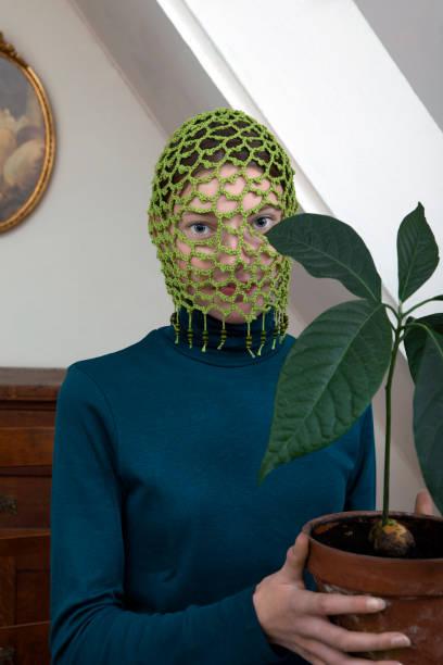 Portrait of teenage girl wearing crocheted green headdress holding potted avocado plant