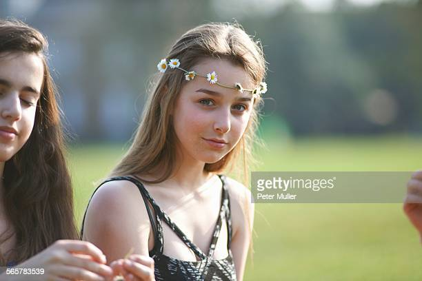 Portrait of teenage girl wearing daisy chain headdress in park