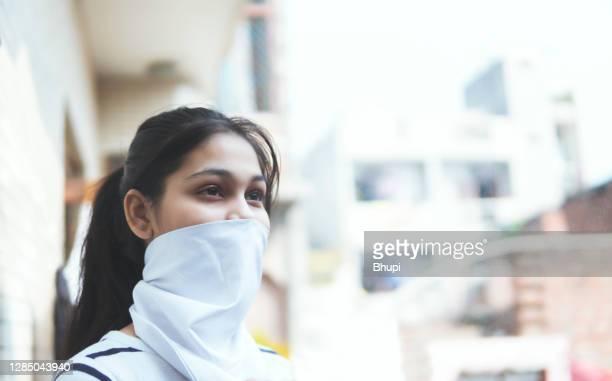 フェイスマスクとしてスカーフで覆う顔を身に着けている10代の少女の肖像。 - ゲートル ストックフォトと画像