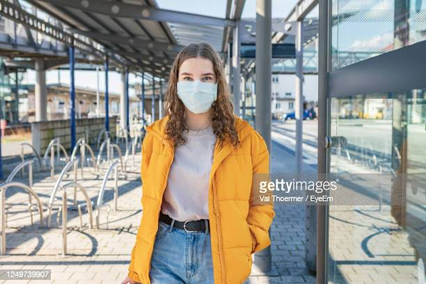portrait of teenage girl wearing mask while standing at entrance - val thoermer stock-fotos und bilder