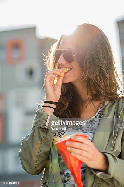 Portrait of teenage girl wearing sunglasses eating French Fries