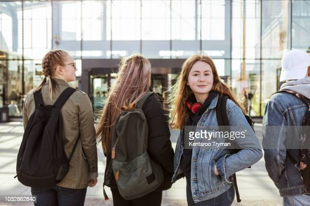 portrait of teenage girl with friends against railroad station in city - tiener stockfoto's en -beelden