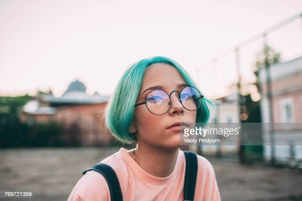 portrait of teenage girl with green dyed hair wearing eyeglasses - tienermeisjes stockfoto's en -beelden