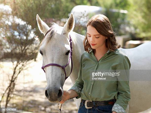 Portrait of teenage girl with grey horse on farm