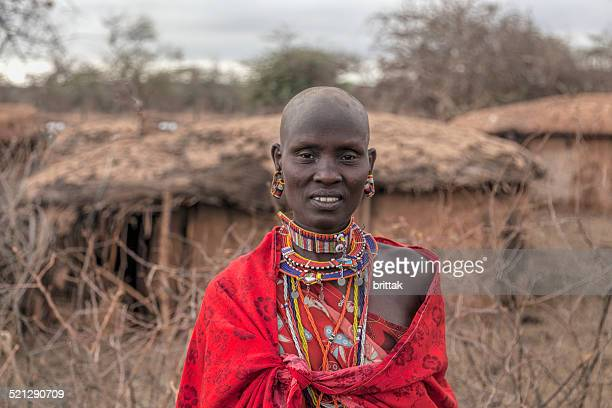 Portrait of teenage Maasai girl in traditional dress outside hut.