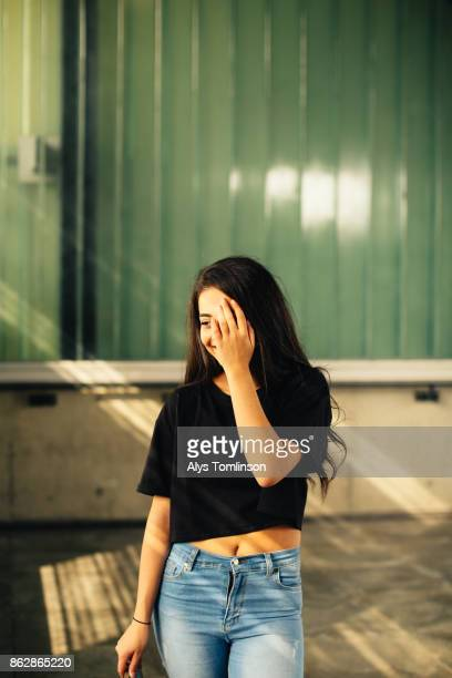 portrait of teenage skatebaord girl with hand held to face - black hair stock pictures, royalty-free photos & images