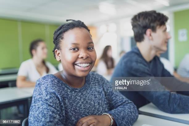 Retrato de adolescente estudiante sonriente en aula