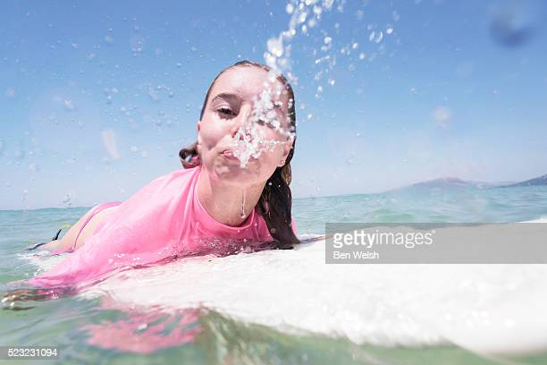 Portrait of teenage surfer (16-17) lying on surfboard and spitting water
