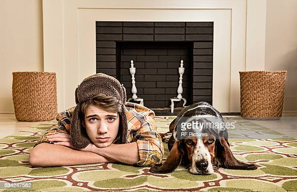 Portrait of teenager (13-15) and dog laying on carpet