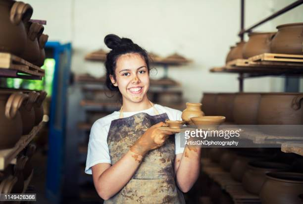 portrait of teenager holding clay vessels at workshop. - potter stock pictures, royalty-free photos & images